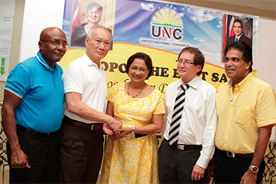 """Prime Minister Kamla Persad-Bissessar greets former Clico chairman Gerard Yetming, second left, and former Senate president Timothy Hamel-Smith, second right, after they showed up at a UNC""""foot soldiers"""" mobilisation meeting in Debe on Tuesday. Also in photo are Oropouche East MP Dr Roodal Moonilal and UNC campaign manager Rodney Charles, left. PHOTO: RISHI RAGOONATH"""